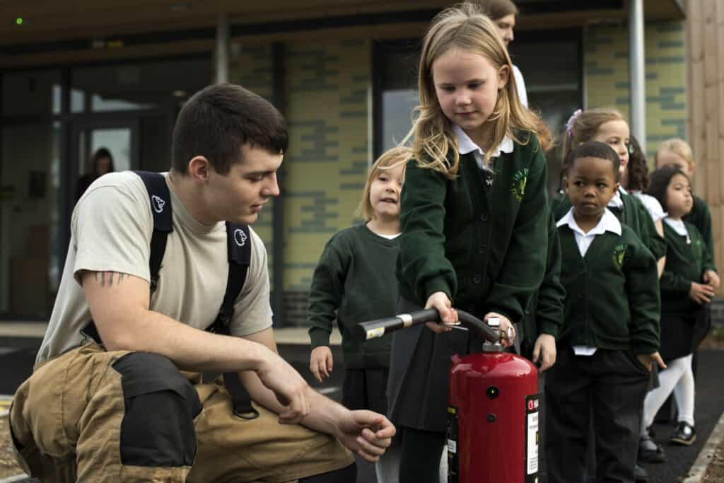 Airman 1st Class Darian Robley, 48th Civil Engineer Squadron firefighter, shows students how to use a fire extinguisher during an Everyday Heroes event at Pines Primary School in Red Lodge, England, Nov. 5. The firefighters taught the children skills to help in the event of an emergency, such as how to use fire extinguisher with the PASS system: Pull the pin, Aim at the base of the fire, Squeeze the trigger, and Sweep side to side. (U.S. Air Force Photo/ Senior Airman Malcolm Mayfield)